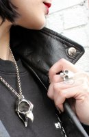 girl with red lipstick, black hair wearing a black leather jacket and Hjälte Jewellery's silver owl skull necklace and silver skull ring