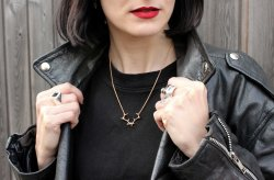 girl with red lipstick, black hair wearing a black leather jacket and Hjälte Jewellery's antler necklace
