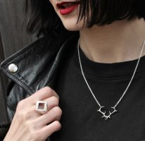 girl with red lipstick, black hair wearing a black leather jacket and Hjälte Jewellery's silver antler necklace and square hollow signet ring