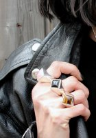 hand wearing a rose quartz square ring, an onyx square ring and a tiger eye square ring whilst holding a leather jacket