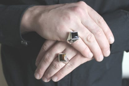 man hands wearing a square onyx signet and a square tiger eye signet