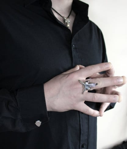 man in black shirt wearing Hjälte jewellerys silver goat skull pendant and goat skull ring