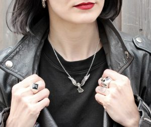 girl with red lipstick, black hair wearing a black leather jacket and Hjälte Jewellery's silver flying barn owl necklace and skull ring and black onyx ring