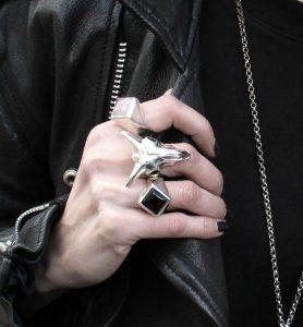 hand weraing three rings, rose quarts, onyx and goat skull