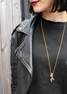 girl with red lipstick, black hair wearing a black leather jacket and Hjälte Jewellery's gold and black rhodium bee necklace