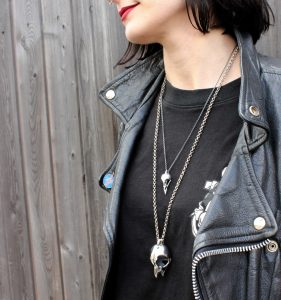 girl with red lipstick, black hair wearing a black leather jacket and Hjälte Jewellery's owl skull and small bird skull jewellery