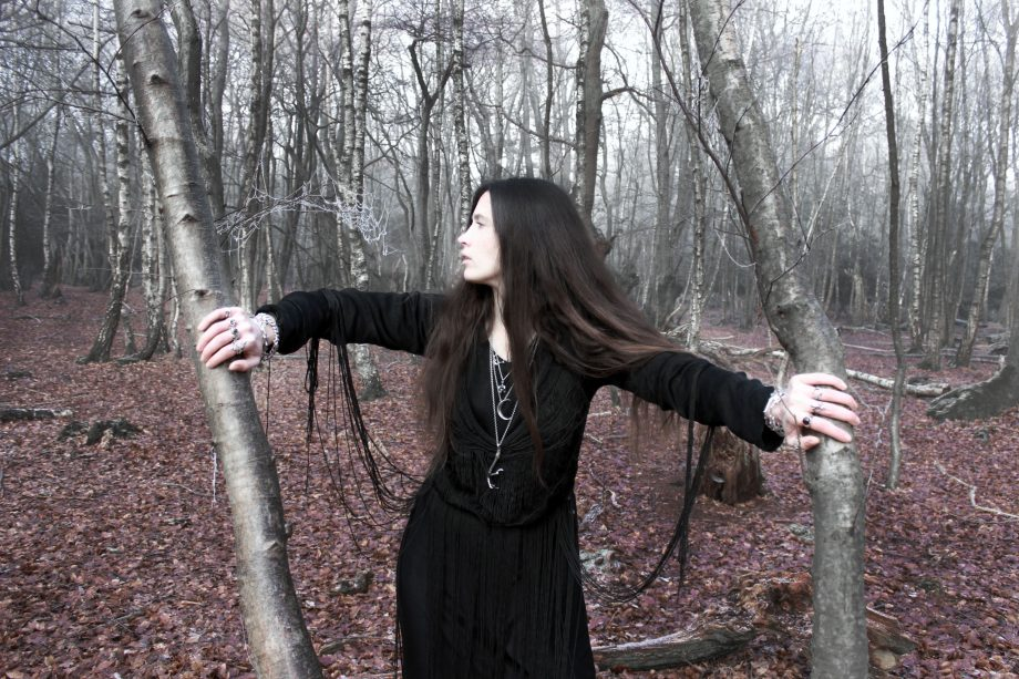 Woman dressed in black in misty woodland between two trees