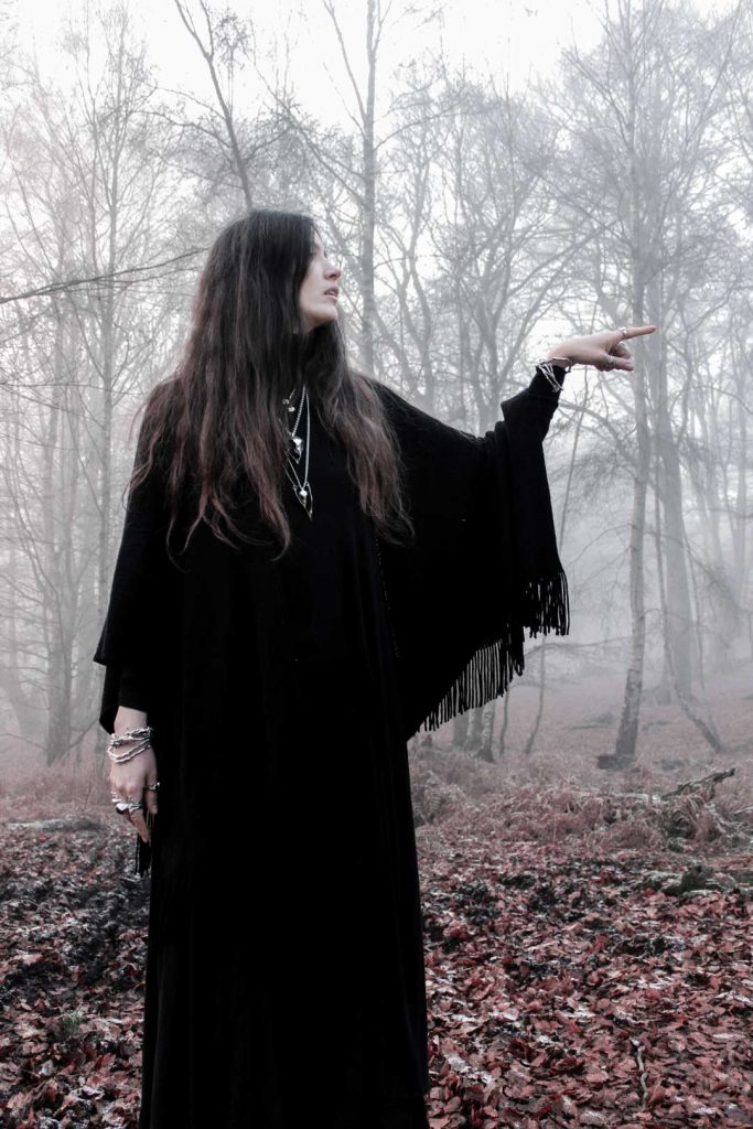 Woman dressed in black in misty woodland pointing to something off-camera